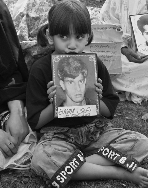 A Kashmiri muslim girl during a demonstration displays a photograph of her elder brother who was subjected to enforced disapperance by Indian troops in Srinagar, Indian occupied Kashmir. ©Faheem Qadri