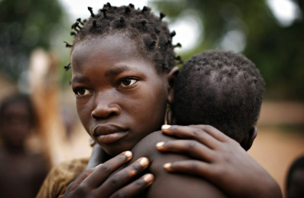 A 12 year old girl, displaced by conflict, holds her baby sister. Image care of Reuters photographer Finbarr O'Reilly